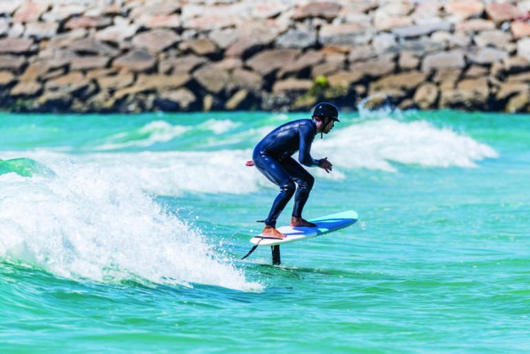 Surfer riding waves water sport trends 2021 Hidrofoil surfer